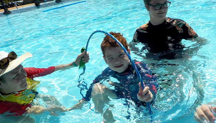 A swim instructor in the pool with a student going through a hoop