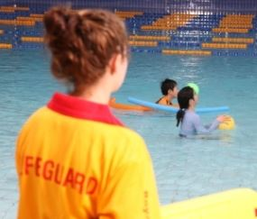 image of lifeguard watching children in a pool