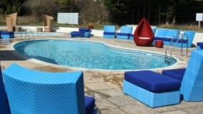 A swimming pool with chairs