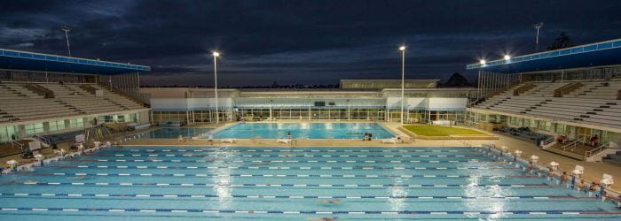 Image of Beatty Park Swimming Pool at night showing large and small pools and grandstand
