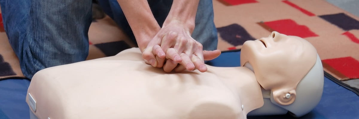close up of person practising CPR on a manikin