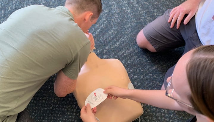 close up of people practising CPR on a manikin