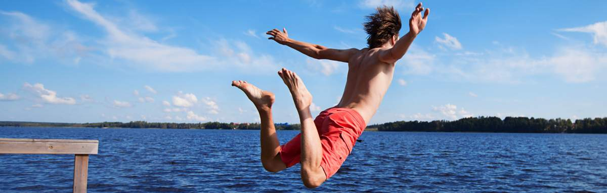 Image of young man jumping into a lake with arms spread wide