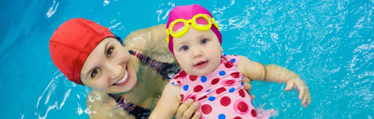 Image of mum with red swim cap on holding baby girl in spotted bathers, pink swim cap and yellow goggles floating on back in a pool