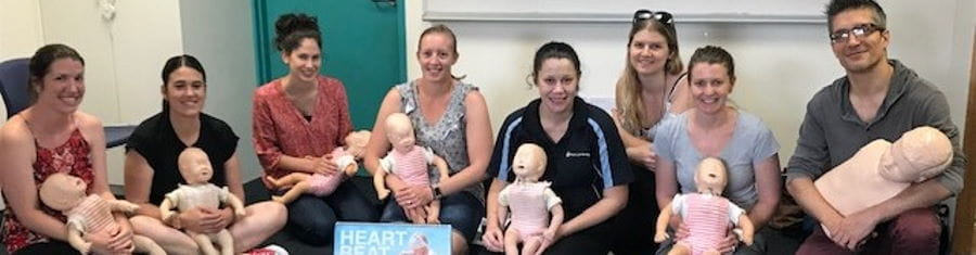 A group of parents with a Keep Watch presenter holding baby manikins