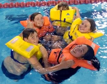 Children wearing lifejackets while in the pool smiling