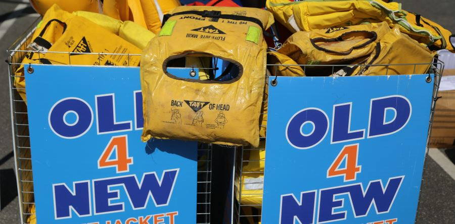 Old yellow foam lifejackets in a basket with an Old 4 New Lifejacket sign