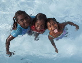 Three aboriginal girls in a swimming pool smiling