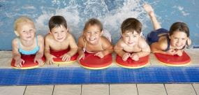 5 Children by the side of the pool with kick boards ready to swim