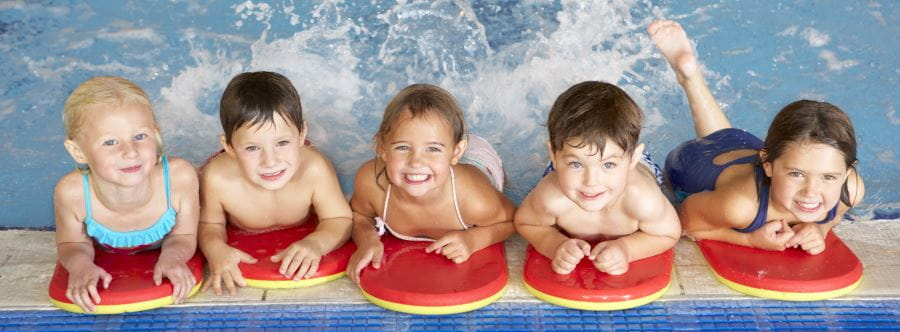 Five children leaning on the edge of the pool with red kickboards, smiling at the camera