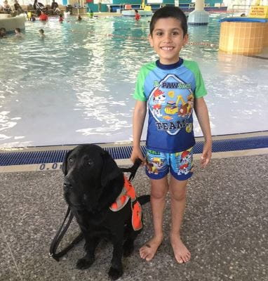 Comet the autism assistance dog with Adam by the pool at Swan Active Beechboro