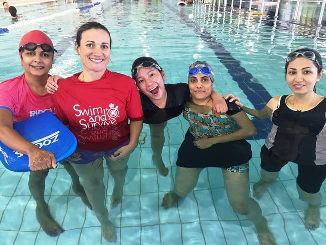 Image of multicultural women in a pool with their instructor