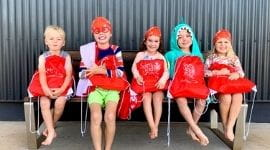 5 children post swim lessons sitting on bench