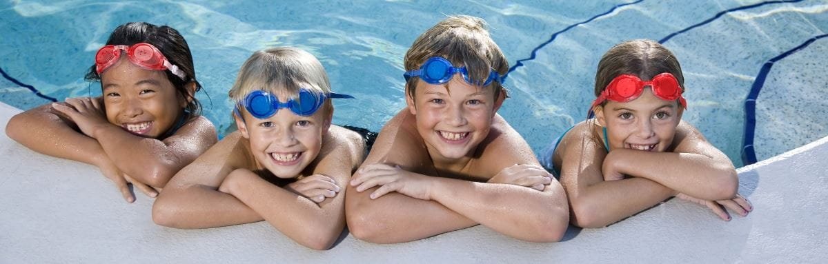 Image of 4 children leaning against the edge of a pool, wearing goggles on their head and smiling at the camera