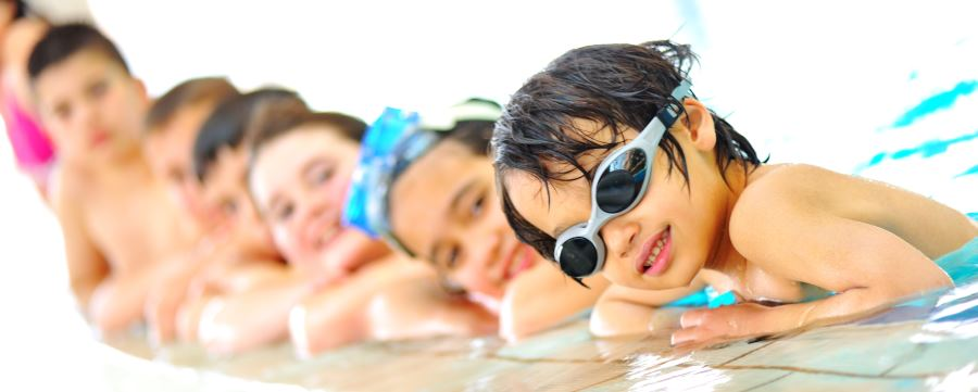 Children in a pool lining up along the edge with goggles on