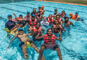 A group of aboriginal youth in the pool with their trainer at Jigalong