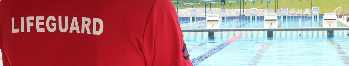 close up of the back of a lifeguard supervising an outdoor swimming pool