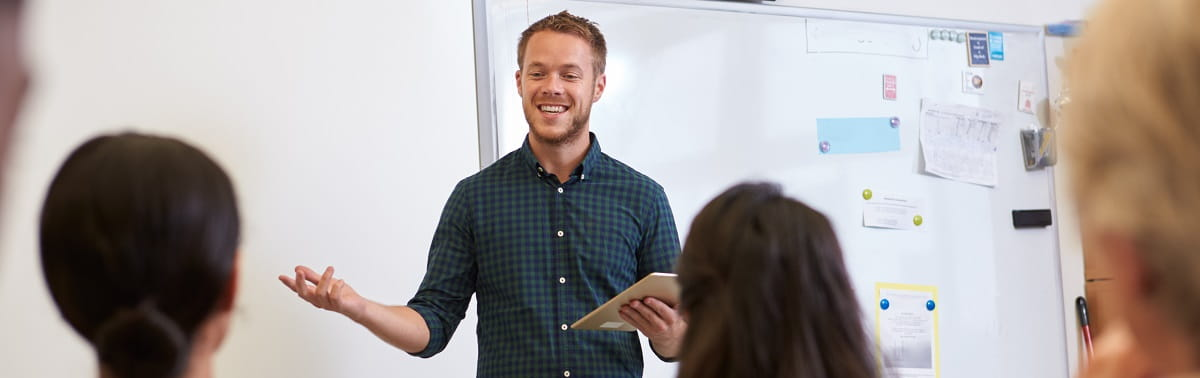 male teacher standing at front of class of high school students