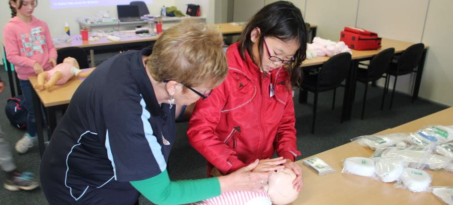 A young girl wearing a red jacket learning CPR on an infant manikin with a Royal Life Saving instructor teaching her