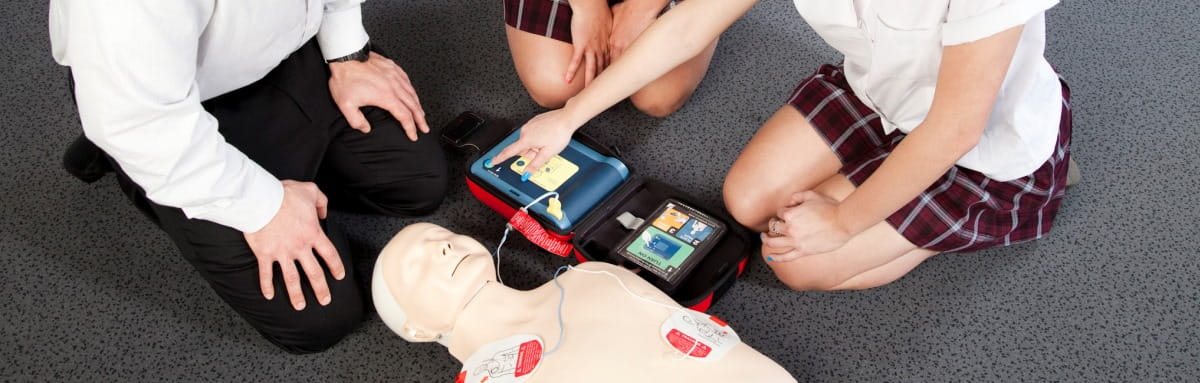 image of people gather around a CPR manikin attaching a defib