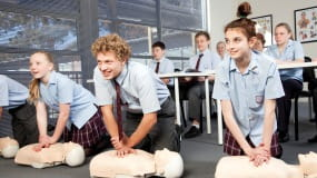 Three school students practicing CPR on a resuscitation manikin