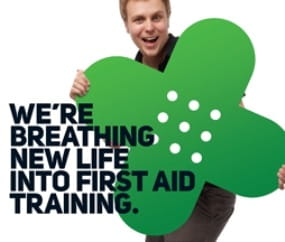 Man holding green first aid cross and the words, we're breathing new life into first aid training