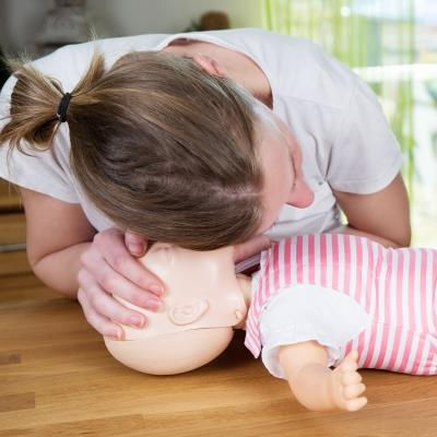 Image of woman with ear close to infant manikin's mouth listening for breathing