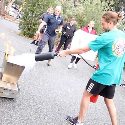 A student showing how to use a fire extinguisher