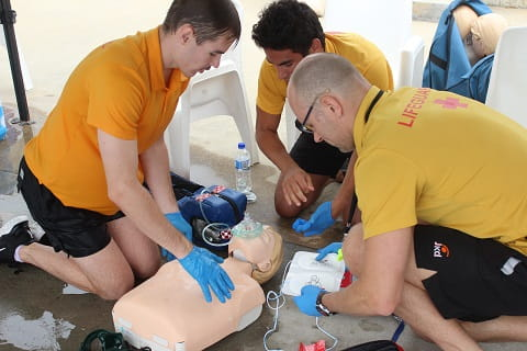 group of lifeguards practising CPR on a manikin