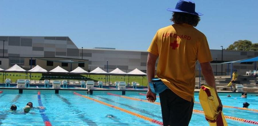 a lifeguard by the pool carrying a rescue tube