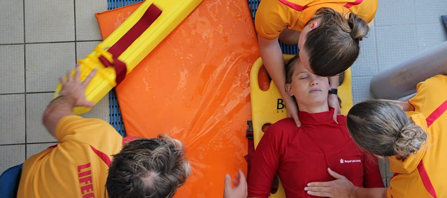 three lifeguards practising spinal injury management