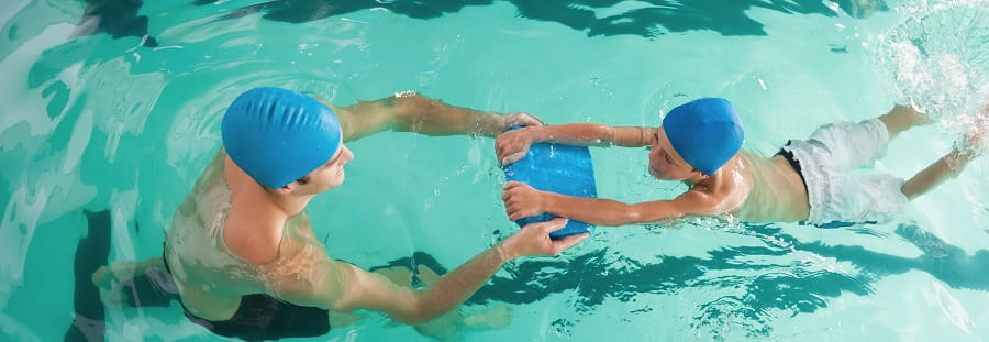 swimming teacher with student doing breaststroke