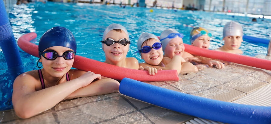 group of children in swimming caps and goggles