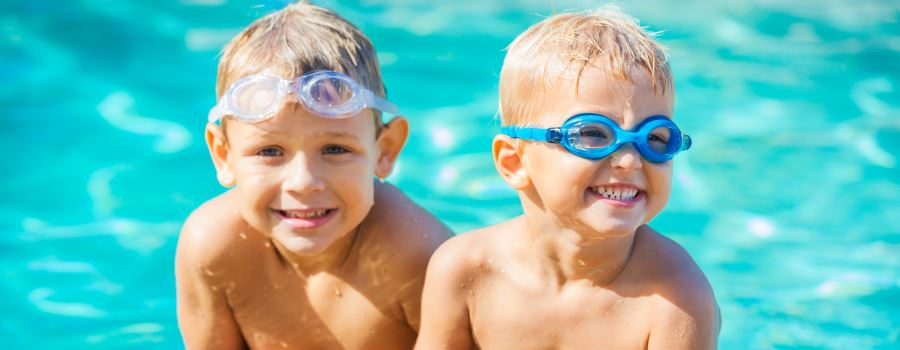 Two blond-haird little boys in a pool wearing goggles