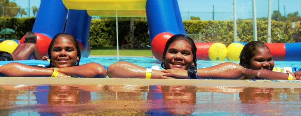 three aboriginal girls smiling from a swimming pool