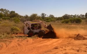 A bobcat digging in red dirt