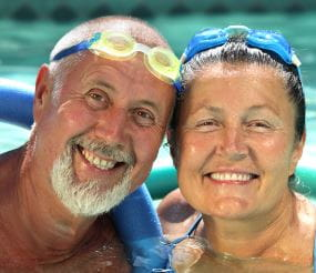An elderly man and woman with goggles on their head in a pool