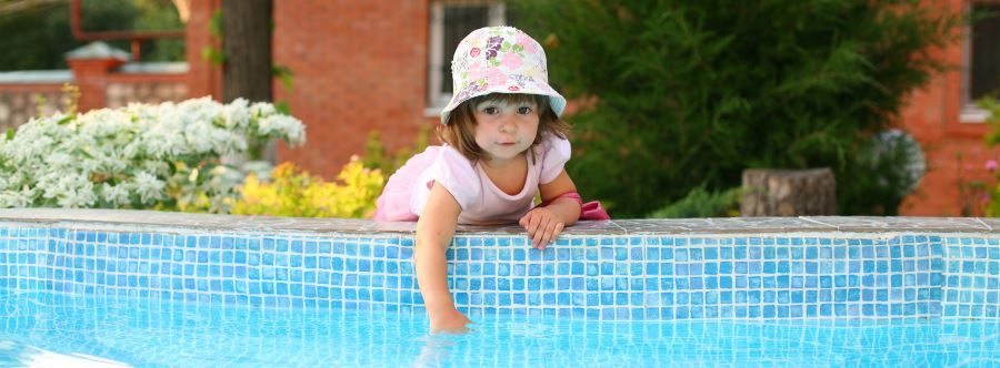 A toddler girl leaning over the edge of a pool putting her hand in the water