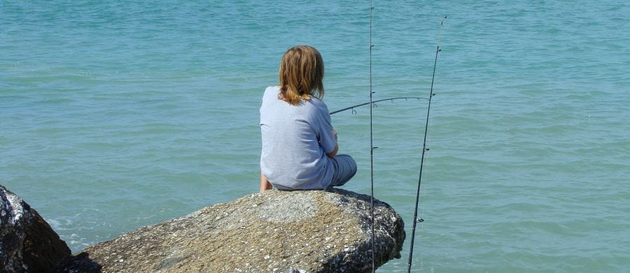 A boy sitting on a rock, fishing by the ocean