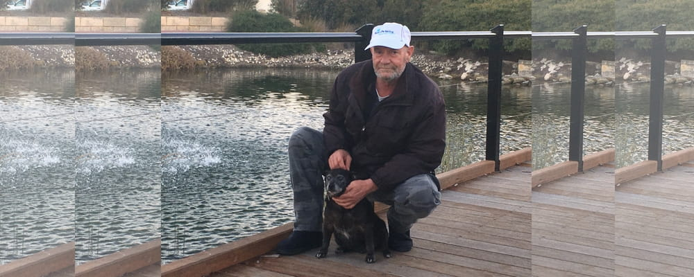 MIchael Faassen and his dog Rocket sit on a footbridge where Rocket recently was rescued.