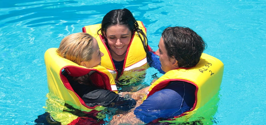 three bronze medallion students in the pool with lifejackets on