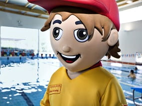 Lifeguard mascot standing at the edge of pool