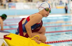 A young girl wearing goggles and holding a lifeguard rescue tube, crouching on the blocks by the pool