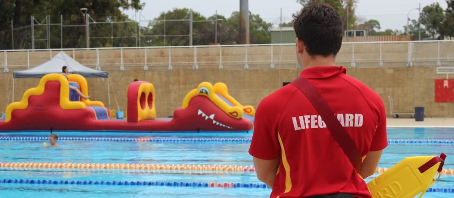 A lifeguard with back to the camera wearing a red shirt and holding a rescue tube, standing by the pool with a large pool inflatable in the distance