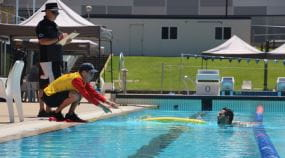 A judge watching over a lifeguard pulling a swimmer from the pool at the Pool Lifeguard Challenge