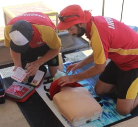 image of two lifeguards performing defibrillation on a CPR manikin
