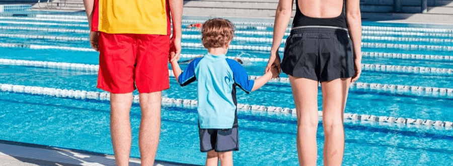lifeguard and parent holding hands with a little boy next to a swimming pool