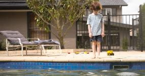 A little boy standing by the pool looking down at the water
