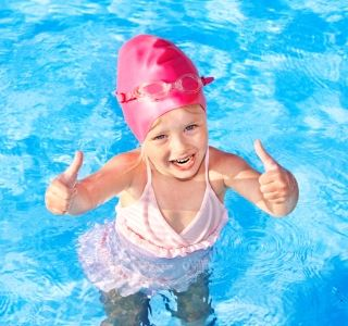 Image of young girl wearing pink swim cap, bathers and goggles giving the two thumbs up sign while in the pool