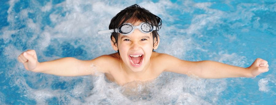 A boy jumping out of the water with arms spread wide and looking very happy